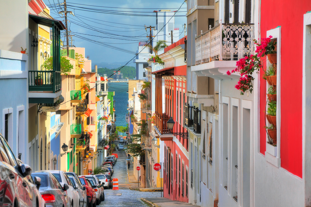 gorgeous view down a colorful street in puerto rico with balconies filled with flowers. view overlooks water